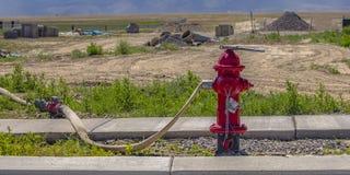 Rode brandkraan met aangesloten slang en moersleutel stock foto's