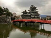 Rode brug over het meer die tot het Kasteel van Matsumoto leiden Royalty-vrije Stock Afbeelding