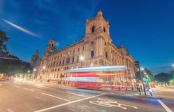 Rode Bus die de straat kruisen bij nacht in Londen Royalty-vrije Stock Foto