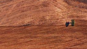 Rode cabinetractor die het gebied met groene ploeg ploegen, satellietbeeld stock footage