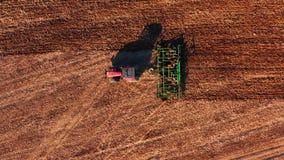 Rode cabinetractor die het gebied met groene ploeg ploegen, satellietbeeld stock videobeelden