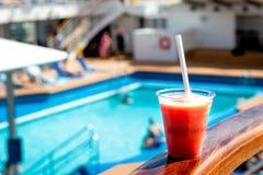 Rode cocktaildrank in de pool stock afbeelding