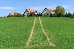 Rode dakhuizen op een groene heuvel royalty-vrije stock afbeeldingen