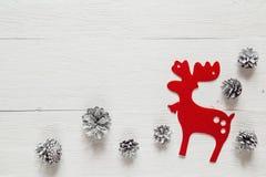 Rode decoratieve herten en sneeuw geschilderde denneappels op rustiek wit Royalty-vrije Stock Afbeelding