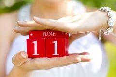 Rode decoratieve kubussen met aantallen ` 11 ` en woord ` juni ` in handen van meisje Royalty-vrije Stock Fotografie