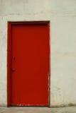 Rode deur in een gebroken witte gipspleistermuur Stock Fotografie