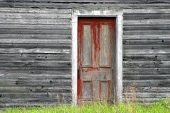 Rode deur op oude houten muur stock foto