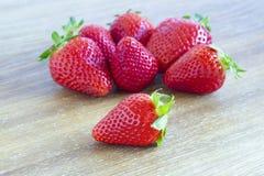 Rode die aardbeien in groep één hen in close-up op de houten lijst wordt geïsoleerd als achtergrond royalty-vrije stock afbeelding