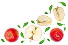 Rode die appelen met plakken met groene die bladeren worden verfraaid op witte hoogste mening als achtergrond met exemplaarruimte Stock Foto's