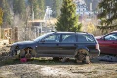 Rode die auto in recreatiestreek wordt geparkeerd en oude roestige gebroken afvalauto na neerstortingsongeval zonder wielen op ho royalty-vrije stock afbeelding