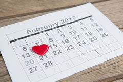 Rode die hartvorm op 14 februari-datum van de kalender wordt geplaatst Stock Foto