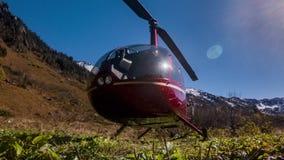 Rode die helikoptertribunes in de bergen op de weide worden geparkeerd stock videobeelden