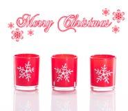 3 rode die kaarsen, kaarshouders met kristalsneeuwvlokken op weerspiegelende witte perspexachtergrond worden geïsoleerd Royalty-vrije Stock Fotografie