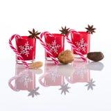 Rode die kaarsen, kaarshouders met kristalsneeuwvlokken, suikerrieten, anijsplantsterren en noten, op weerspiegelend wit perspex  Royalty-vrije Stock Foto's