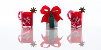 Rode die kaarsen, kaarshouders met kristalsneeuwvlokken, suikerrieten en anijsplantsterren en een giftdoos, op weerspiegelende wi Stock Afbeelding