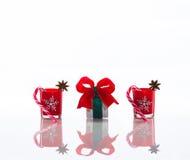 Rode die kaarsen, kaarshouders met kristalsneeuwvlokken, suikerrieten en anijsplantsterren en een giftdoos, op weerspiegelende wi Royalty-vrije Stock Foto's