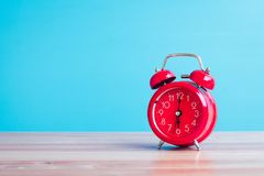 Rode die klok op houten lijst aangaande blauwe achtergrond wordt geplaatst stock fotografie