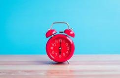 Rode die klok op houten lijst aangaande blauwe achtergrond wordt geplaatst stock foto