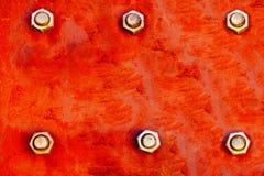 Rode die metaalplaat met sterke rode en oranje kleuren wordt geschilderd en vast met zes grote schroeven van de staalbout als tex royalty-vrije stock afbeeldingen