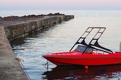Rode die motorboot bij de pijler wordt vastgelegd stock afbeeldingen