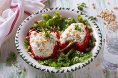 Rode die paprika's met ricotta, knoflook en kruiden worden gevuld Stock Afbeeldingen