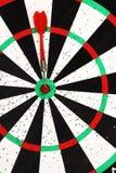 Rode die pijltjepijl in het doelcentrum wordt geraakt van dartboardachtergrond stock foto