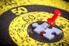 Rode die speld aan de puzzelstuk van de mensenvorm wordt gehouden op oude doelraad Stock Fotografie