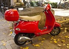 Rode die Vespa op stoepstraat wordt geparkeerd Stock Afbeelding