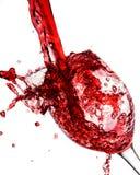 Rode die wijn in wijnglas wordt gegoten Stock Foto
