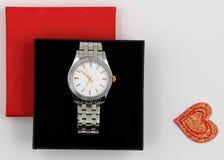 Rode doos met zilveren horloge stock foto