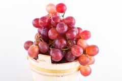 Rode druiven in een rustieke houten emmer op witte achtergrond Royalty-vrije Stock Afbeeldingen