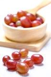 Rode druiven in houten kom en lepel Stock Afbeelding