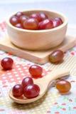 Rode druiven in houten kom en lepel Royalty-vrije Stock Foto's