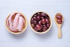 Rode druiven in houten kom en lepel Royalty-vrije Stock Afbeelding