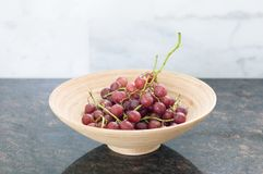 Rode druiventakjes in een houten kom op een granietlijst meer dan licht g royalty-vrije stock foto
