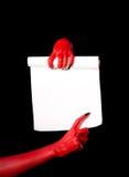 Rode duivelshanden die document rol houden stock foto