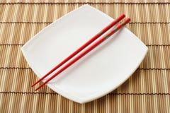 Rode eetstokjes en witte schotel op een bamboeservet Stock Foto
