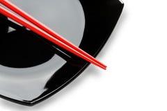 Rode eetstokjes op een zwarte schotel. Variant twee. Royalty-vrije Stock Afbeelding