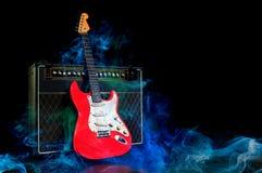 Rode elektrische die gitaar en versterker door rook wordt omringd stock afbeeldingen