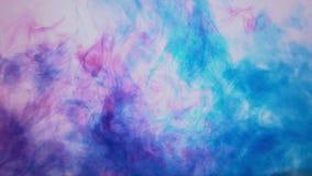 Rode en blauwe die inkt in water wordt gemengd stock footage