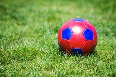 Rode en blauwe fotball op gras stock afbeelding