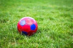 Rode en blauwe fotball op gras stock foto