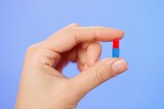 Rode en blauwe hap (capsule) in artsenhand royalty-vrije stock fotografie