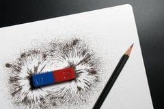 Rode en blauwe magnetische barmagneet of fysica, potlood en ijzer pow stock afbeeldingen