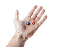 Rode en blauwe pillen op geïsoleerde hand Stock Afbeelding