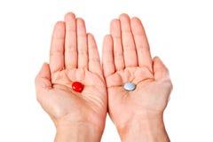 Rode en blauwe pillen in vrouwenhanden Stock Foto's