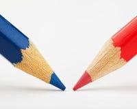 Rode en blauwe potloden tegen elkaar op een Witboek Stock Afbeeldingen