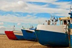 Rode en blauwe vissersboten op de kust Stock Afbeeldingen
