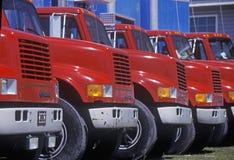 Rode en blauwe vrachtwagens op een rij stock afbeeldingen