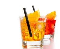 Rode en gele cocktail met oranje die plak op bovenkant en stro op witte achtergrond wordt geïsoleerd Stock Foto